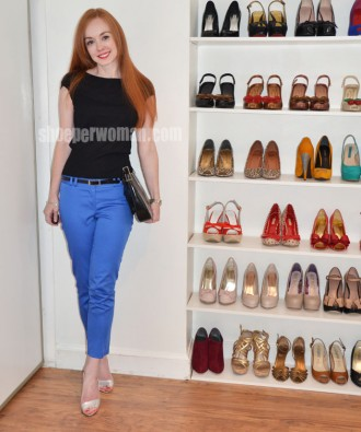 Redhead in bright blue trousers and high heels