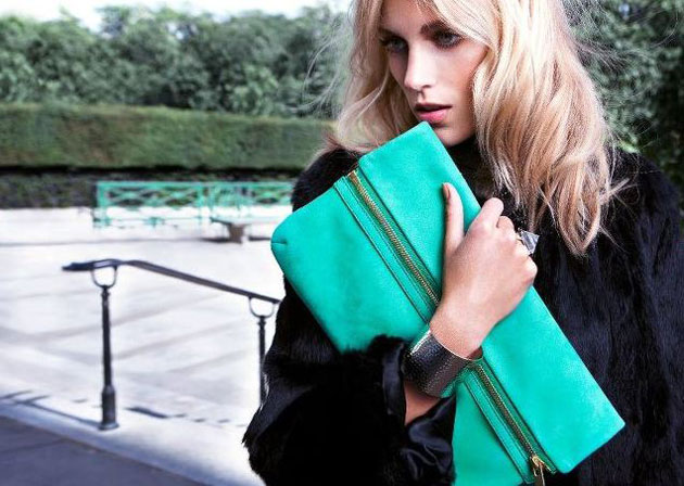 Model with bright green oversized clutch bag
