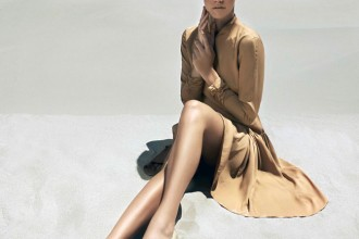 Model in tan dress and gold flat shoes