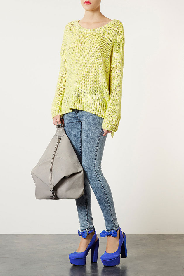 blue platform shoes worn with acid wash jeans and neon yellow sweater